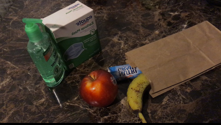 Image of food alongside a box of masks and hand sanitizer. Students can pick up food at Morton East. Testing locations require the use of a mask and will provide h和 sanitizer.